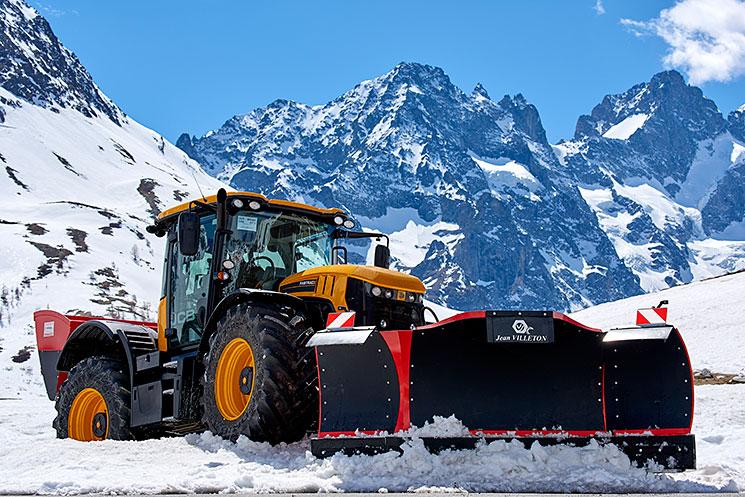 Engin équipé d'une lame tri-axiale en action sur une route de montagne enneigée